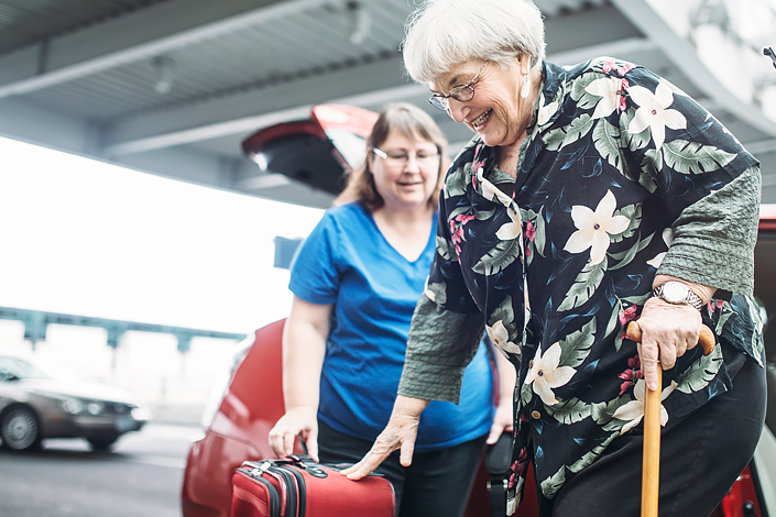 A woman at an airport provides assistance to a woman of age, helping her get out of a car and carrying her baggage