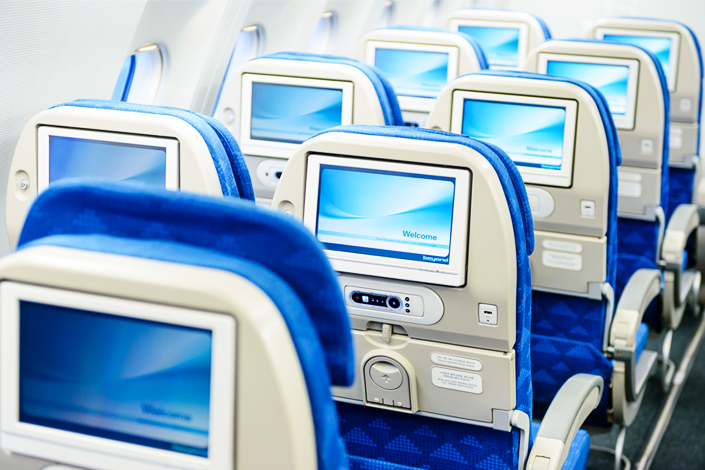 Filas de asientos de pasajeros vacíos con pantallas a bordo de un avión