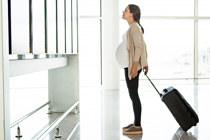 A young pregnant woman with baggage watching the airport departure and arrival signboard in a departure hall of an airport